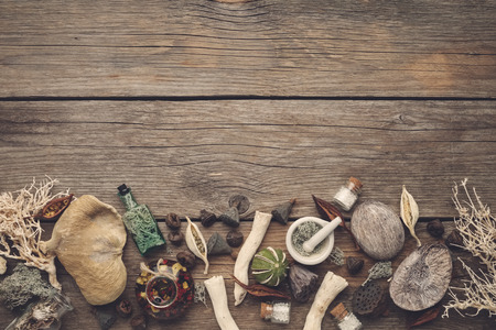 Dried moss, dry roots, nut shell, coconuts, plants, eucalyptus, lotus seeds, bottles of infusion and homeopathic globules, mortar and pestle. Stock Photo