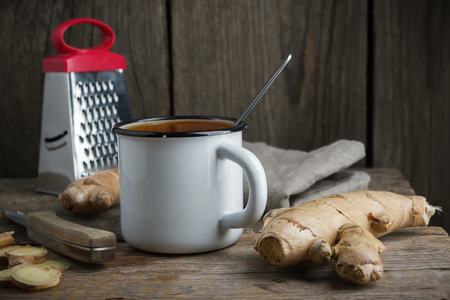 Healthy ginger tea cup, ginger root and grater on wooden table.