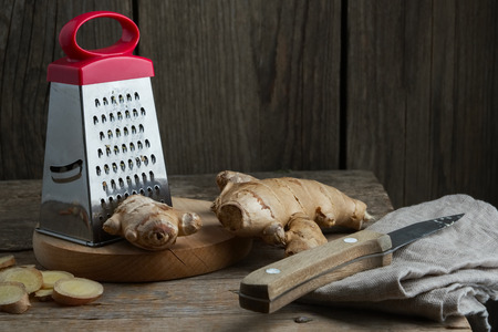 Ginger root and grater on kitchen table. Stock Photo