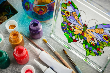 Artisan painting with stained glass paints on a glass.