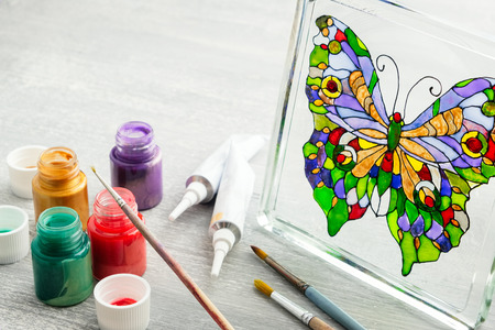 Artisan painting with stained glass paints on the glass surface. Stock Photo