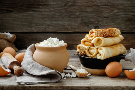 Frying pan of baked pancakes, ingredients and kitchenware for pancakes making on wooden kitchen table. Stock Photo - 120977757