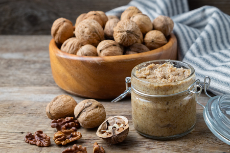 Glass jar of raw organic walnut butter or paste and fresh nuts in bowl on table.