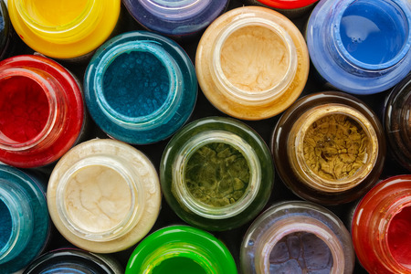 Colorful stained glass paints or oil, acrylic paints close up, top view.