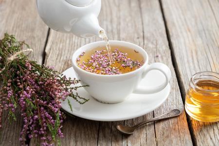 Gesunder Heidetee gegossen in weiße Tasse. Teekanne, kleines Honigglas und Heidekraut. Standard-Bild