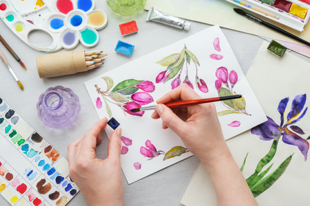 Painter holding a paintbrush in his hand. Watercolor drawing - pink cherry flowers - and artistic equipment on desk. Top view. Painter drawing at working place.