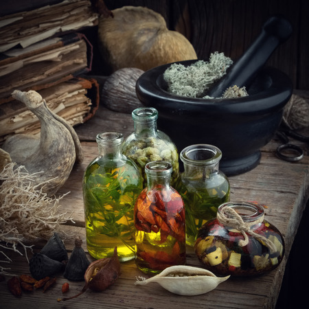 Bottles of essential oil or potion, mortar of dried moss, old books, dry roots and plants. Herbal medicine.