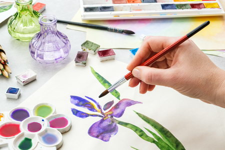 Painter holding a paintbrush in his hand. Watercolor drawing - Iris flower and artistic equipment on desk. Top view. Painter drawing at working place.