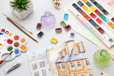 Watercolor drawing - view of the roofs of houses. Artistic equipment on desk. Top view.