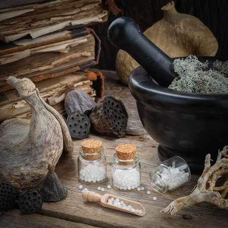 Bottles of homeopathic globules, mortar, dried moss, old books, dry roots, nuts and plants on table. Homeopathy medicine. Stock Photo - 120977710