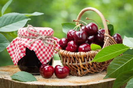 Jar of jam and basket of sweet cherries on background in garden outdoors.