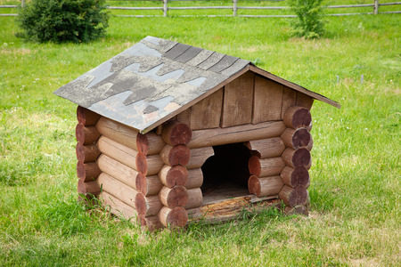 Wooden dog house  on green lawn. Stock Photo