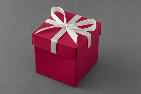 Red luxury gift box with ribbon on gray Фото со стока