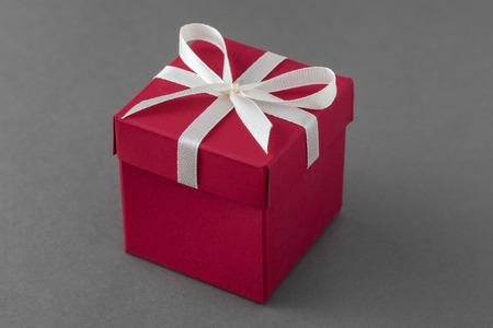 Red luxury gift box with ribbon on gray 版權商用圖片