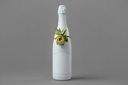 Wedding champagne bottle with blank label. Bottle decorated with roses, pearls and ribbon. Copy space for text.