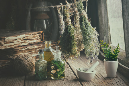 Infusion bottles, old books, mortar and hanging bunches of dry medicinal herbs.