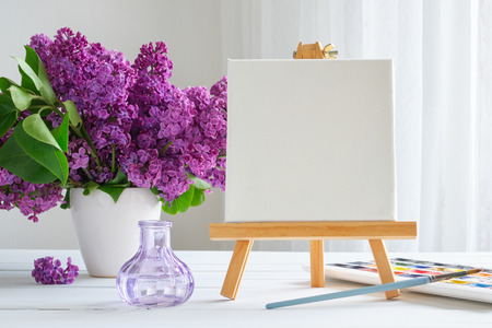 Blank canvas on easel, watercolor paints, brush for painting and lilac flowers on table.