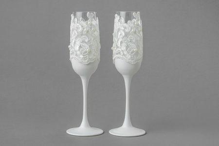 Two white wedding wine glasses decorated with lace and pearls.