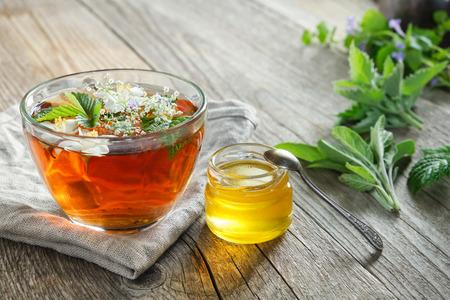 Gezonde kruidenthee beker, honingpot en geneeskrachtige kruiden op oude houten tafel.