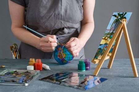 Painter holding a paintbrush in his hand and painting with stained glass paints on a glass vase.