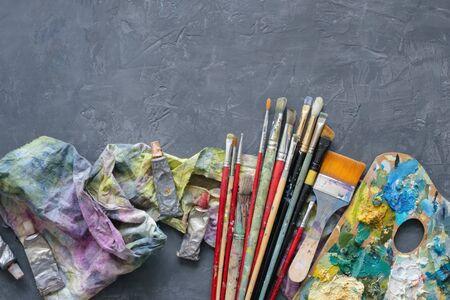 Artist paint brushes, palette, palette knifes, paint tubes on gray concrete