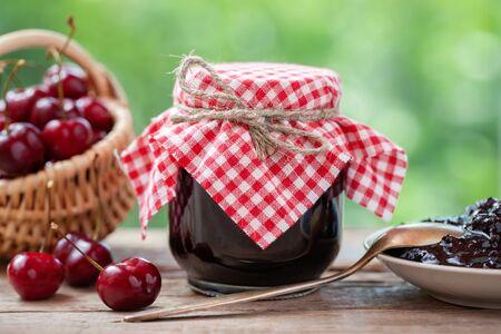 Pot kersenjam, mand met kersen, schotel en lepel op tafel buiten. Stockfoto