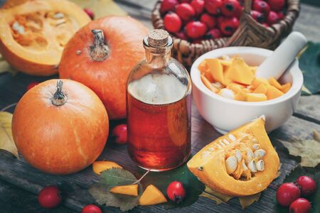 Pumpkin seeds oil bottle, pumpkins, mortar and basket of  hawthorn berries on wooden table with autumn leaves.