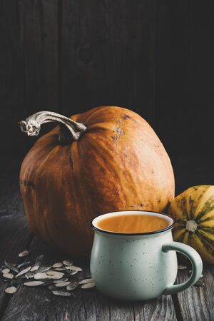Cup of fresh pumpkin juice, ripe pumpkins and seeds on wooden table.