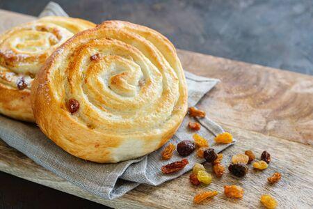 Freshly baked bun with raisins on a linen napkin.