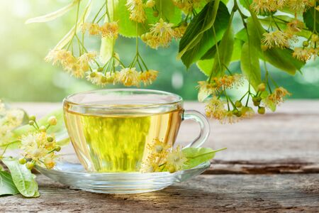 Glass cup of healthy tea with linden tree flowers on wooden board, lime tree flowers. 版權商用圖片