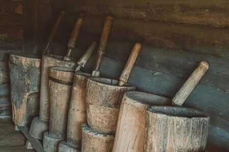 Old wooden mortars with pistils in them. Old home utensils  for grains grinding.