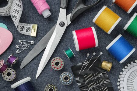 Sewing items: tailoring scissors, measuring tape, thimble, spools of thread, including pins, needles and sewing accessories on sewing cloth.
