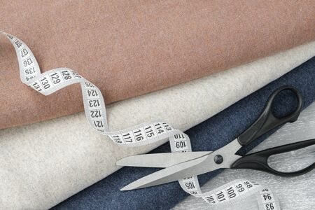 Colorful knitted fabrics, scissors and measuring tape.