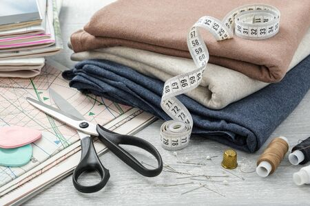 Sewing items: colorful fabrics, scissors, measuring tape, thimble, spools of threads, including pins, chalks, sewing pattern and magazines on a tabletop.