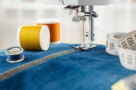 Cucire jeans in denim con macchina da cucire. Primo piano dell'ago della macchina da cucire sul punto del tessuto denim, bobine di fili e nastro di misurazione. Archivio Fotografico