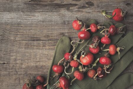 Rose hip berries, sweet briar fruits, gloves on wooden board. Top view. 版權商用圖片
