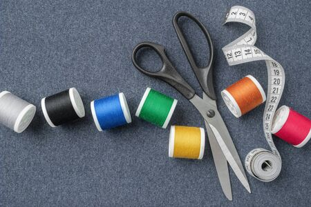 Sewing items: tailoring scissors, measuring tape, spools of multicolored threads.