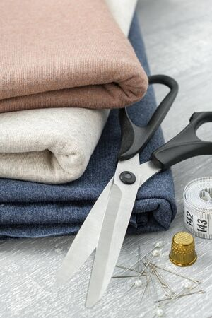 Sewing items: fabrics, tailoring scissors, tape measure for sewing clothes.