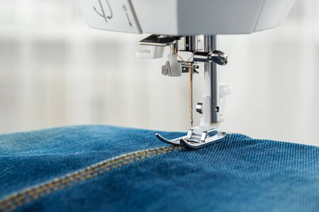 Sewing denim jeans with sewing machine. Close up of needle of sewing machine on the denim fabric stitch.