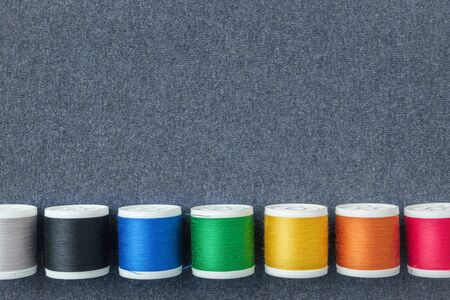Row of spools of multicolored threads on sewing cloth. View from above. Copy space for text.