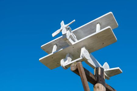 Small wooden plane on blue sky
