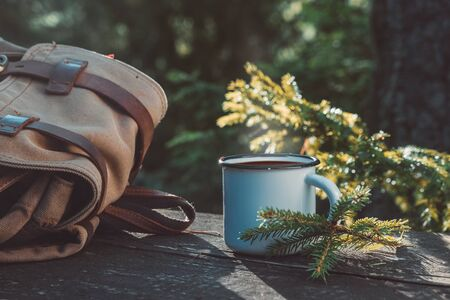 Enameled cup of coffee or tea, backpack of traveler on wooden board in summer forest outdoors. 版權商用圖片