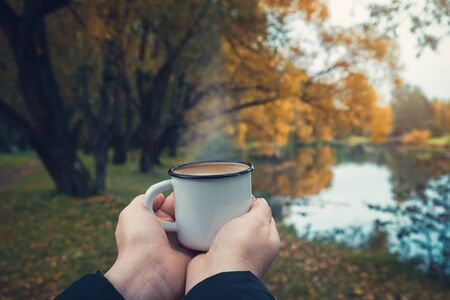 Female hands hold a enameled cup of coffee on autumn landscape outdoors.