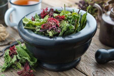 Black mortar of medicinal herbs,  enameled cup of healthy herbal tea and vintage tea kettle on background.