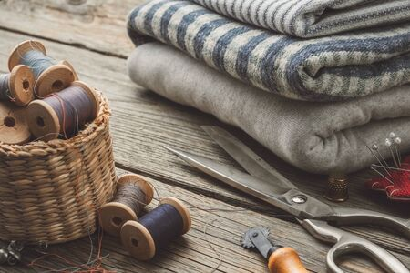 Sewing items: retro tailoring scissors, thimble, cutting knife, basket with wooden spools of thread, cushion for including pins and stack of fabrics.