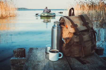 Enameled mug of coffee or tea, backpack of traveler on wooden pier on tranquil lake.