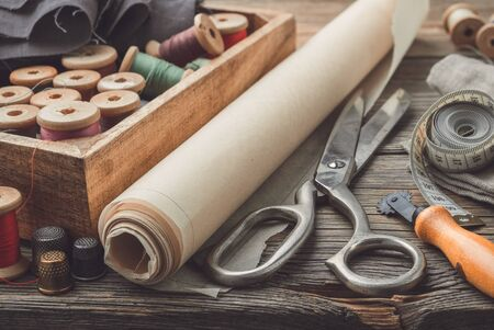 Sewing items: retro tailoring scissors, measuring tape, thimble, vintage spools of thread in wooden box, patterns on paper and tailor cutting knife.