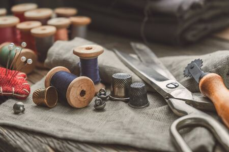 Retro sewing items: tailoring scissors, cutting knife, thimble, wooden thread spools, cushion for including pins, fabrics and sewing accessories. 版權商用圖片