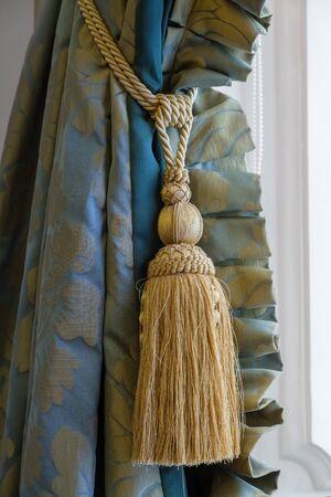 Gland de luxe de couleur dorée en gros plan et beau rideau.