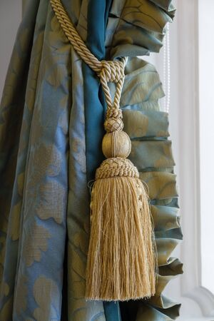 Luxury tassel in golden color close up and beautiful curtain. 版權商用圖片